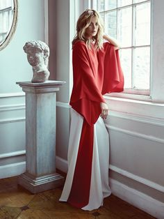 Posing next to a marble statue, Carolyn wears red blouse with red and white trousers from Ralph Lauren