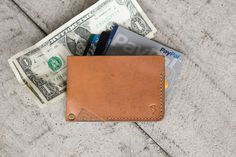 Keep it slim and simple. Perfectly sized to slip in your front pocket, this minimalist leather wallet will hold up to 10 cards and folded cash, while an interior divider keeps things manageable. Made of vegetable tanned leather, these wallets are built to last and age beautifully. You won't be throwing this one out after one season of use, it will last for years to come. Made of 4 oz veg tanned leather from the US tannery, Herman Oak. Each wallet is hand-dyed, double stitched and finished…