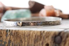 hand stamped personalized sterling silver bangle bracelet with golden heart.