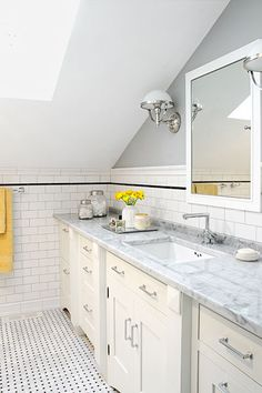 A skylight in this windowless master bath ushers in much-needed natural light. Subway tile and a Carrara-marble-topped vanity upgrade the dated 1988 addition.