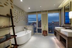 This beautiful Asian spa in spired master bathroom is the place to relax in this on-the-go city. Twenty six floors above the Las Vegas Strip, this bathroom feels like a quick trip to their orient. The double sink vanity is custom made from zebra wood, which gives the space a more authentic look. A large soaker tub is tucked away behind a small wall so that bathers can still enjoy the view from the sky, but are also given a bit of privacy. The space also helps to give it that private, spa…