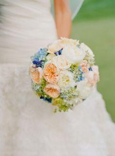 Beautiful bouquet of light blue hydrangea, blue lace cap hydrangea, peach juliette roses, white peony, message roses, blue delphinium, alchemilla, and cream vendella roses.
