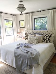 Neutral bedroom. Window behind bed. Farmhouse bedroom. Bedroom window treatments. Bedroom lighting. Black windows. Benjamin Moore Windsbreath