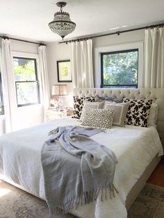 Neutral bedroom. Window behind bed. Farmhouse bedroom. Bedroom window treatments. Bedroom lighting. Black windows. Benjamin Moore Windsbreath