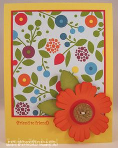 "Create a 3 D Paper Flower; punch out two tangerine tango flowers;  use paper snips to cut into each of the petals.  Sponge the edges.  Tape the centers together and gently separate the petals.  Add leaves using blossom petal builder punch; add 1"" real red circle to center.  Old Olive button"