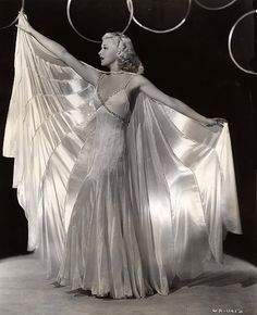 Ginger Rogers wearing an evening gown and cape, designed by Bernard Newman for…