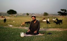 A Pakistani Muslim man offers the daily Asr prayer, the afternoon prayer, near his goats feeding in a field on the outskirts of Islamabad, Pakistan, Monday, Sept. 24, 2012. [Credit : Muhammed Muheisen/AP]