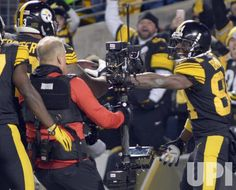 Pittsburgh Steelers wide receiver Antonio Brown (84) hands the football to Pittsburgh Steelers guard Ramon Foster (73) so he can strike the…