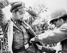 A captured SS NCO being searched by a US soldier during Operation 'Cobra'. Waffen-SS formations were regarded as the best German forces in Normandy. Most were deployed in the British sector, but the Americans faced 2nd SS Panzer Division and 17th SS Panzergrenadiers. OWIL 52255.