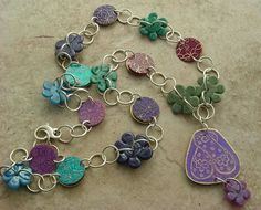 Love this necklace in purple, turquoise, blue, and green. Lisa Liddy made it with her own etched disks and flower Lampwork beads by Susan Sheehan. MonaRAEbeads.etsy.com