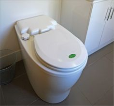 A photo shows a self-contained composting toilet that looks only slightly different to a conventional flush toilet. It has a larger outside chamber, and no visible cistern.
