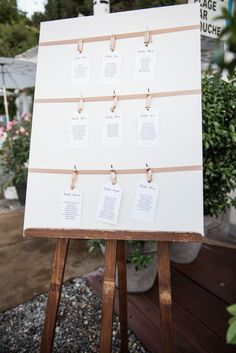 Traditional seating chart with sating ribbon & pegs -   Image by Julie Michaelsen Photography - A humanist outdoor back garden wedding ceremony with huge floral arch. Destination english wedding in France with reception at Paloma Beach in Nice.
