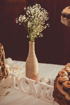 Rustic wedding centerpiece idea - wine bottles wrapped in twine and filled with baby's breath / http://www.himisspuff.com/rustic-wedding-centerpiece-ideas/13/