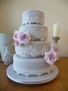Silver wedding cake with sugarveil lace and pale pink and lilac handmade roses, designed by Kristina Medd at Penn Wedding Cakes