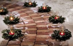 What a gorgeous way to decorate a walkway around the holidays: tiny wreaths, candles in mason jars, and a light dusting of snow. #winterdecor #wreaths #masonjars