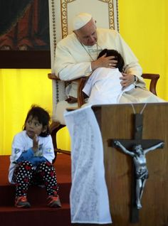 Pope Francis embraces a child as he meets with prisoners and their children inside Palmasola prison in Santa Cruz, Bolivia, Friday, July 10, 2015. The pope urged inmates at the notoriously violent prison to not despair as he wrapped up his visit to Bolivia with a message of hope and solidarity for those caught up in Bolivia's corrupt law enforcement system. (AP Photo/Gregorio Borgia)