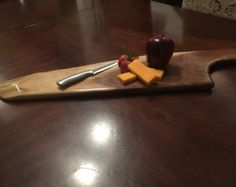 This Large Cutting Board is handcrafted from solid Walnut. It uses the natural contours of the wood to form the shape of a knife. It has a live edge on one side. It also has a braided leather strap for hanging. This is a beautiful and unique board that will be a great conversation piece. Hard to find one like it. It will look great in any kitchen or dining room. The pictured item is the actual piece you will receive. Dimensions: 37.5 Total Length 24 Length of Cutting Space 5.5-7.75 Width…