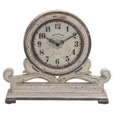 "Add artful appeal to your desk or mantel with this eye-catching table clock, showcasing a scrolling base and distressed finish.  Product: Table clock Construction Material: Engineered woodColor: Antiqued ivoryFeatures:  Scrolling baseRoman numeral dialAccommodates: Batteries - not included Dimensions: 16"" H x 15"" W x 4"" D"