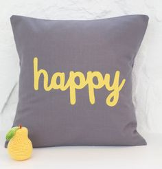 Share some happiness with this cushion cover!    The word happy is cut from a bright yellow cotton fabric to contrast with the grey cotton cushion