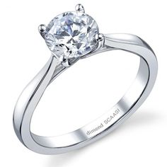 Classic Solitaire diamond ring featuring curvy, feminine lines leading to the elegant head allowing full view of the diamond's profile. Two become one, as the head bars swoop so beautifully to hold its diamond. Thin and delicate and made to fit with just about any wedding band. Check out JULIET her 6-prong cousin.
