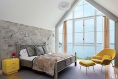 The master bedroom of this Shelter Island, New York, retreat by Michael Haverland and decorator Philip Galanes is lined with a Carolyn Ray wallpaper; the Saarinen chair and ottoman are by KnollStudio.