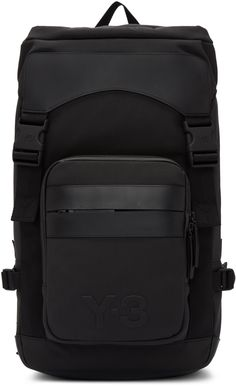 Structured textile backpack in black. Tonal buffed leather trim throughout. Grosgrain carry handle at top. Adjustable padded shoulder straps with waist straps. Zippered compartment at face featuring zip pocket and debossed logo. Adjustable cinch strap at sides. Padded panel at back featuring cut-out accents and embossed logo. Zippered laptop compartment at back face. Foldover flap at main compartment with fixture straps. Two-way zip closure. Patch and zip pockets at interior. Approx. 11.5