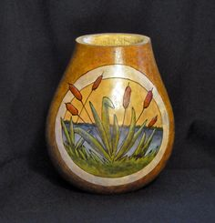 A quiet scene beside a lake, with cattails growing on the near shore, spilling out of their circular frame is the scene on this natural gourd vase. The natural beauty of real gourds invites this sort of design. Nature attracts nature. The wood burned design of cattails growing beside a lake was dyed, not painted, to allow the natural markings of the gourd to show through.  The sky is the natural color of the gourd, with brown and green cattails, blue water, and a light brown overall. This…