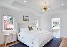 Absolutely beautiful bedroom features a nickel sputnik pendant, Arteriors Zanadoo Chandelier, hanging over a white tufted wingback bed adorned with a leopard pillow flanked by mid century modern nightstands and glass lamps tucked under windows.