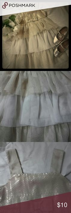 Cherokee dress sz 4T Gold and cream sparkled and ruffled cherokee dress 4T. Bottom layers are made from tulle. Gold portion has sparkles while the cream portion is a solid color. Sleeveless. Bow in middle. Sequin top. Elastic in the back. My oldest daughter wore this in my wedding. Great for the holidays or special occasions! Cherokee Dresses