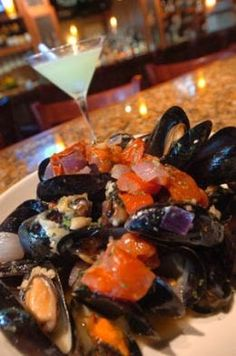 3 dozen fresh mussels 1-3/4 cups chopped tomatoes 1/4 cup licorice flavored liquor 1/2 cup chopped yellow onion fresh basil 1/2 lemon, juice...
