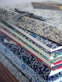 Liberty print fabric covered notebooks. They look so pretty stacked up together!