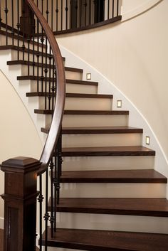 Interior wooden stairs with metal railing and floor lights