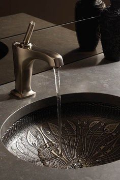 Bathroom stainless steel undermount sink with artistic design on surface.