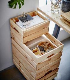 Les caisses IKEA KNAGGLIG, empilées, servent de rangement aux fournitures.