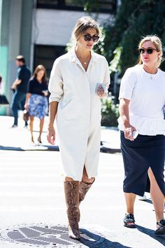 A white shirtdress is paired with knee-high snake-print boots