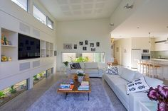 The living room has a polished concrete floor and soaring ceiling.