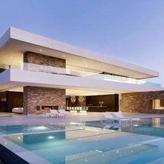 Casa com guarda corpo em vidro e acabamento branco e em pedra e piscina frontal.