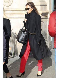 自身がデザインを手掛ける「ヴィクトリア・ベッカム」の最新コレクションから、ウエストのチェーンがアクセントになった黒のコートをチョイス。ロング丈と背中のプリーツが今年らしいデザインのコートに、ヴィヴィッドな赤のパンツを合わせてハンサムに着こなして。「マノロ ブラニク」のピンヒールで決めた華奢な足元が、女性らしさを引き立てるポイントに。