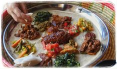 Delicious Ethiopian food is placed on the injera within the moseb basket
