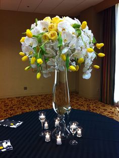 The entry piece will be a large white modern vase overflowing with yellow tulips, yellow garden roses, yellow hydrangeas and white phalaenopsis orchids.  Very similar to this except more yellow and not quite as large as pictured. From Stems Floral Design