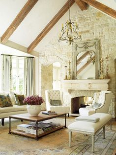 Stone wall and fireplace, wood beams, chairs by fire, mantle....