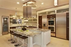 This sleek and stylish open plan kitchen features a gray and white marble-topped island, integrated stovetop, stainless steel appliances and dark brown cabinetry. A stunning contemporary design ties the space together.
