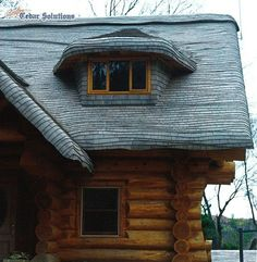 Stained Cedar Shingle Roof on a Log Home. The roof edges have been steam-bent to give the appearance of an old English cottage.