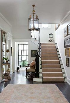 decor and stairwell (A large window at one end of this entry hall opens the space and floods it with gorgeous, natural light - Traditional Home®, seagrass stair runner Design Entrée, House Design, Interior Design, Lobby Design, Hall Design, Design Ideas, Interior Ideas, Design Trends, Hall Deco