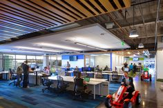 Raw ceiling with nice wood + acoustic paneling, colorful carpet, team-sized working environments