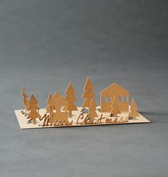 The small outlines on the card can be lifted up to stand up, creating a miniature Christmas village to place on a mantle or windowsill. Kraft brown greeting card on red folding card - with kraft brown envelope.