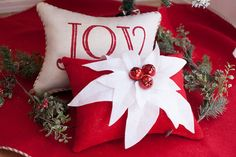 My poinsettia lumber pillow is made of red upholstery grade burlap, white wool felt individually sewn petals, and hand sewn red bells. Comes already stuffed, no insert needed. Pillow measures approx. 12 x 16.  Listing is for pillow only.  All products come wrapped in ribbon, with store tag and a bow. This is especially nice for those items that are gifts!  All products are lovingly hand made in my smoke-free studio.  All products, ideas, photos, packaging, logo, blog etc. © The Burlap…