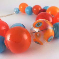 Happy, fresh, light arrangement of orange and turquoise glass bubbles beads. Fine silver. Inlayed wooden case