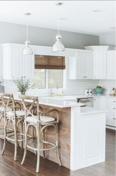 All White Kitchen with Light Wood Stools