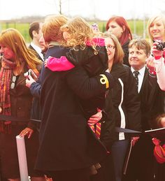 Rupert Grint hugging and lifting up a little girl at a premiere...oh my goodness.